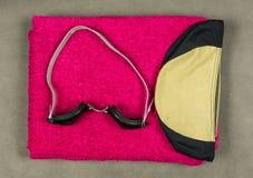 游泳盖帽、游泳的风镜和毛巾 库存照片