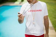 游泳看秒表的教练在游泳池边附近在一个晴天 库存图片