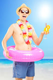 游泳短裤的微笑的人,藏品鸡尾酒和摆在  免版税库存照片