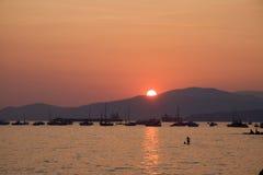 游泳者在作为太阳的水中设置在英吉利湾,温哥华 免版税库存图片