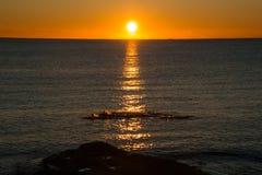 游泳者在日出的海 库存图片