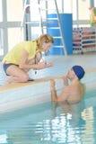 游泳者谈话与教练由游泳池边有空的中心 免版税库存图片
