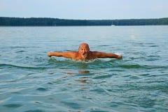 游泳者,老人游泳蝶泳 年岁的白种人男性60年 免版税库存图片