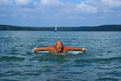 游泳者,老人游泳蝶泳 年岁的白种人男性60年 免版税图库摄影