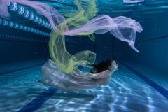 游泳者水下使用与布料 免版税图库摄影