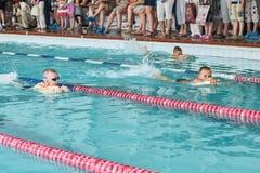 游泳自由式的孩子在游泳的教训 库存照片