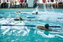 游泳自由式的孩子在游泳的教训 免版税库存图片