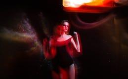 黑游泳衣和圆的玻璃的美丽的女孩隔绝了黑波斯菊背景 空间概念艺术 混杂的光 免版税库存图片