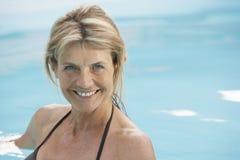 游泳衣游泳的愉快的妇女在水池 免版税库存图片
