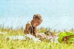 游泳衣的一个女孩孤独坐在草的海滩在河附近在一好日子 女孩是哀伤的在 库存图片