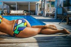 游泳衣的一个性感的女孩,放松在游泳以后,在游泳池附近 库存照片
