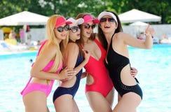 游泳衣的四个女孩在一个色的背景水池 免版税库存照片