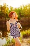 游泳衣的女孩有在湖的一条小狗的 库存照片