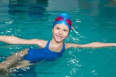 游泳衣的女孩,游泳盖帽,风镜,举行  免版税库存图片