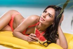 游泳衣的妇女吃西瓜的,当放松在游泳的床垫时 免版税库存图片
