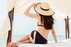 游泳衣的妇女lounging在海滩在她的假期 免版税库存照片