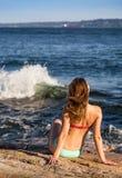 游泳衣的年轻深色的女孩在有波浪碰撞的海洋旁边 免版税库存照片