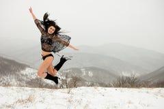 游泳衣的深色头发的女孩在冬天跃迁mounta 免版税库存照片