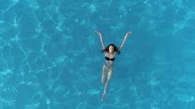 游泳衣的游泳女孩在清楚的水池放松了在夏时,鸟瞰图 股票录像