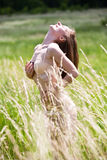 游泳衣的美丽的女孩在草 免版税库存照片
