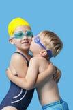 游泳衣的年轻兄弟姐妹拥抱和亲吻在蓝色背景的 免版税库存照片