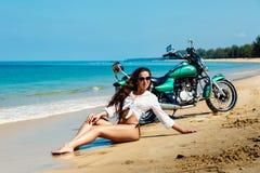 游泳衣的年轻性感的女孩在与摩托车的一个海滩 免版税库存照片