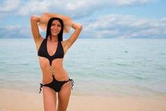 黑游泳衣的年轻美丽的性感的女孩 免版税库存图片
