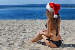 黑游泳衣的年轻,可爱的圣诞老人女孩和帽子在海滩的由海洋 库存图片