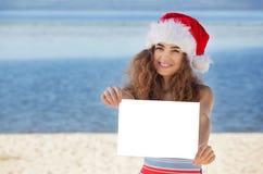 游泳衣的年轻,可爱,卷曲圣诞老人女孩和帽子拿着一张白色纸片的海滩的 免版税库存图片