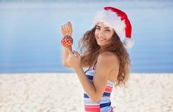 游泳衣的年轻,可爱,苗条圣诞老人女孩和帽子拿着一个红色圣诞节球的海滩的 免版税库存照片