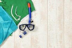 游泳裤、毛巾和潜航的面具在地板 免版税库存照片