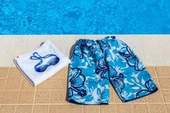游泳裤风镜和毛巾在水池 图库摄影