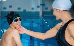 游泳辅导员认真地检查他的学生 免版税库存图片