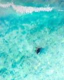 游泳通过蓝色海洋和波浪的海龟的鸟瞰图 免版税库存图片