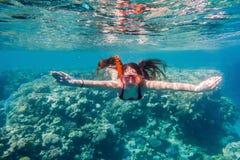 游泳面具潜水的女孩在珊瑚礁附近的红海 库存照片