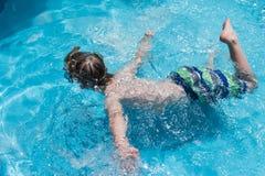 游泳面具的年轻男孩在游泳池水平的布局 库存照片