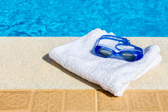 游泳风镜和毛巾在游泳池附近 免版税图库摄影