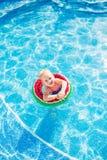 游泳,暑假-使用在大海的可爱的微笑的女孩用lifebuoy西瓜 免版税库存照片