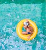游泳,暑假-使用在蓝色wat的儿童男孩 免版税库存图片