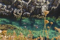 游泳,潜航,在透明的绿松石水中的四个人演奏和探索水下的珍宝  免版税库存照片