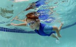 游泳年轻的男孩在水面下 免版税图库摄影