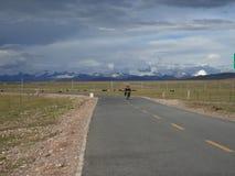 游牧人在天空路骑摩托车在西藏 免版税库存图片