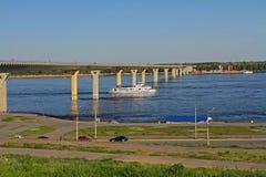 游船在桥梁下通过伏尔加河在伏尔加格勒 免版税图库摄影