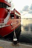 游船,靠码头对岸和被投掷绳索,拿着它在岸附近 免版税库存图片