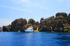 游艇、岩石和蓝色海,选择聚焦,作用掀动转移 库存照片