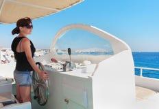 游艇上尉舵的妇女  免版税库存照片