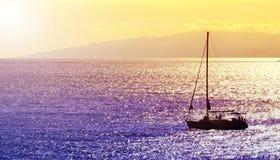 游艇剪影在日落的 反对五颜六色的海洋水和天空的风船在特内里费岛,加那利群岛,西班牙 免版税库存照片