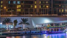 游艇和小船有停留在shoping的购物中心附近和通过在一座桥梁下的游人的在迪拜小游艇船坞区夜 股票视频