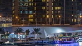 游艇和小船有停留在shoping的购物中心附近和通过在一座桥梁下的游人的在迪拜小游艇船坞区夜 影视素材