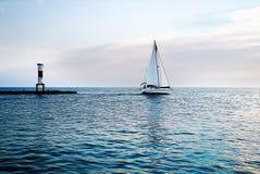游艇和灯塔在日落在蓝色海 白色风帆a 皇族释放例证